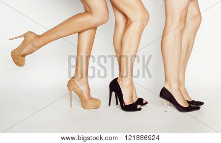 three pair of woman legs in hight heels shoes isolated on white close up