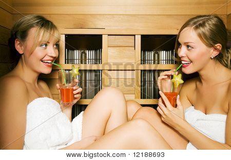 zwei Freunde (weiblich) Vitamin Getränke in einer Sauna genießen