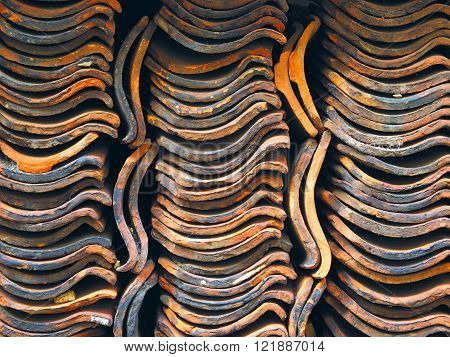 Curved old and used roof tiles in a stack