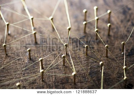 Linking entities. Network, networking, social media, internet communication abstract. A small network connected to a larger network. Web of gold wires on rustic wood.  Network hub or key person.