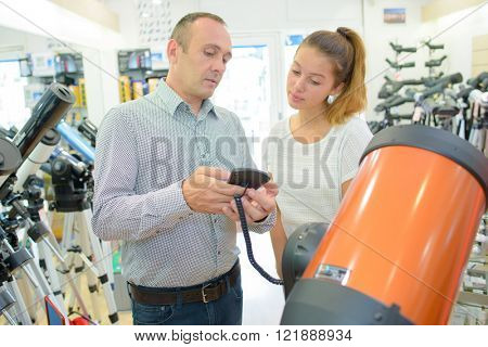 Salesman showing professional telescope to customer