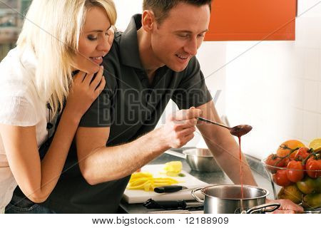 Young couple cooking (in this case: strawberry sauce for dessert)