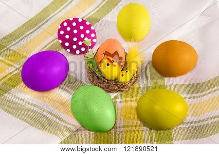 Easter decoration and colorful eggs on checkered cotton napkin.