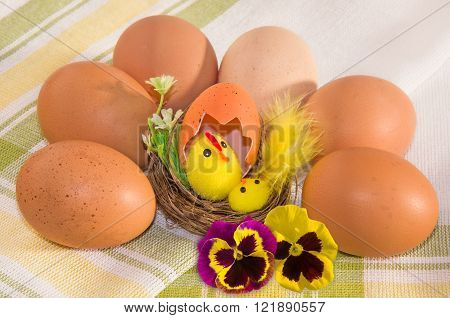 Easter decoration with two flowers of viola tricolor and brown eggs on checkered cotton napkin.