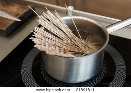 Buckwheat noodles being cooked on induction stove