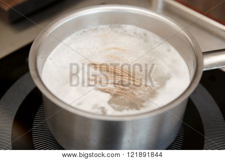 Buckwheat noodles being cooked in boiling water