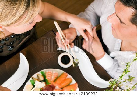 Couple eating sushi for dinner, romantic setting, presumably this is an advanced date; shallow focus on eyes