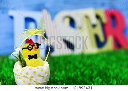 a funny teddy chick, emerging from a dot-patterned eggshell on the grass and three-dimensional letters forming the word easter in the background, against a blue background