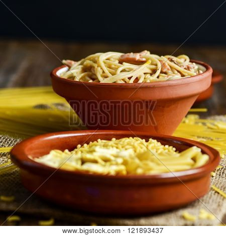 closeup of an earthenware plate with some uncooked pasta and an earthenware bowl with spaghetti alla carbonara, on a table