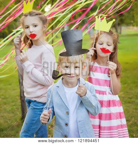 little boy and two girls posing with paper masks on a cheerful children's holiday.