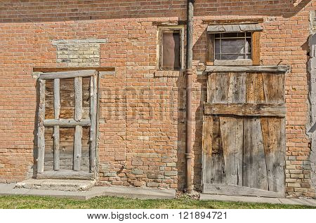Old wood doors on a brick building look like they were an afterthought or are covering spaces where nicer doors had once been.