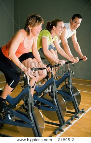 Three People Cycling In A Gym Or Fitness Club, Dressed In Colorful Clothes; Focus On The Mature Woman