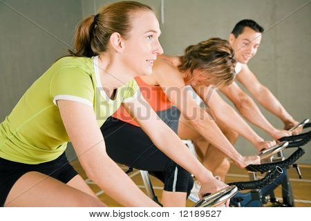 Three People Cycling In A Gym Or Fitness Club, Dressed In Colorful Clothes; Focus On The Girl In Gre