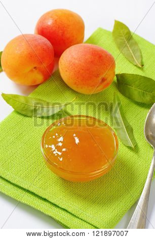 fresh apricots and bowl of apricot jam on green place mat