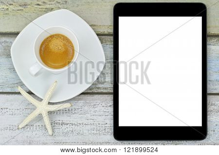 Star fish on freshly brewed espresso coffee next to black tablet computer with white blank screen