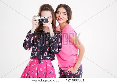 Two cheerful pretty young women taking pictures with vintage camera over white background