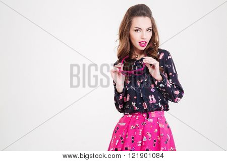 Attracive happy young woman holding pink sunglasses over white background