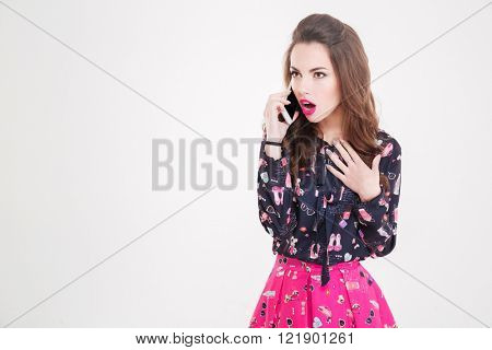 Amazed beautiful young woman talking on cell phone over white background