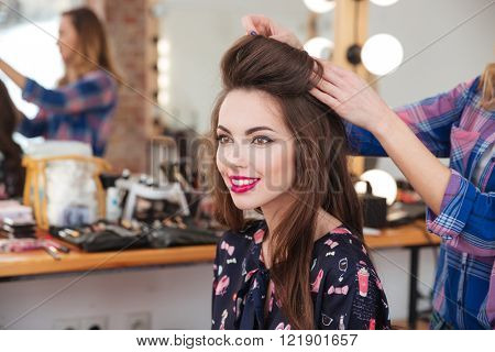 Professional female hairdresser making hairstyle to cheerful young woman with long hair