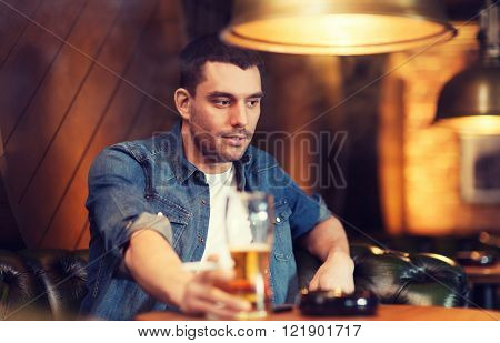 people and bad habits concept - young man drinking beer and smoking cigarette at bar or pub