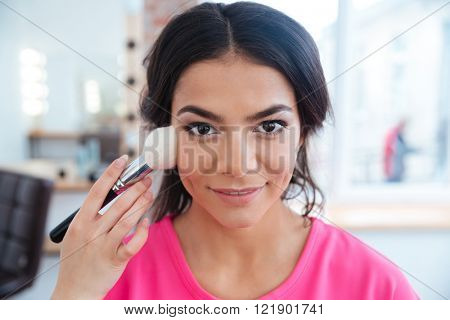 Female makeup artist with brush doing professional makeup to smiling cute young woman in beauty salon