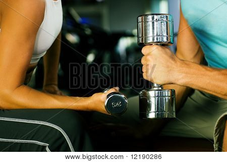 couple in the gym having a workout with dumbbells