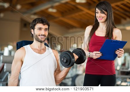 Man working out in a gym while his personal trainer looks at the execution