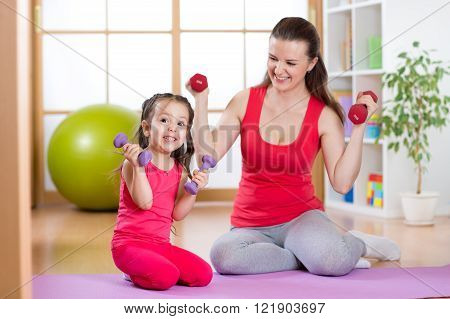 Woman with funny child do exercise lifting dumbbells, healthy motherhood  and parenthood concept