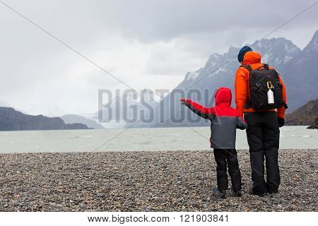 active father and his son enjoying the view of glacier grey at lago grey and having adventure hike at torres del paine national park patagonia chile