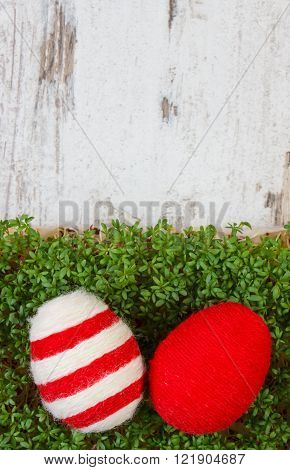 Easter eggs wrapped woolen string and green cuckooflower cress on old wooden background, copy space for inscription or text, decoration for Easter