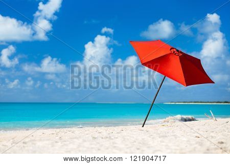 Red umbrella on Idyllic tropical beach with white sand, turquoise ocean water and blue sky at deserted island in Caribbean