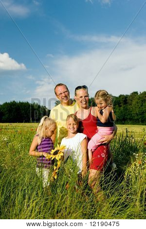 Happy family of five standing in the grass with and flowers together - metaphor for love