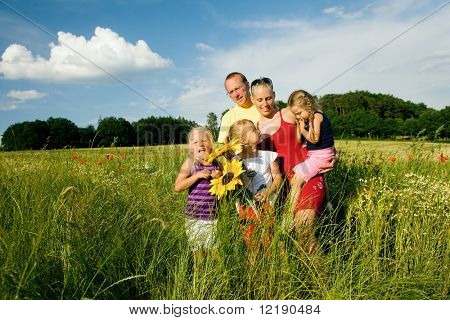 Happy family with tree kids standing in a field of wild flowers together - metaphor for love