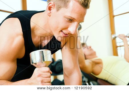Strong man lifting dumbbells in a gym, a woman training on a machine in the background