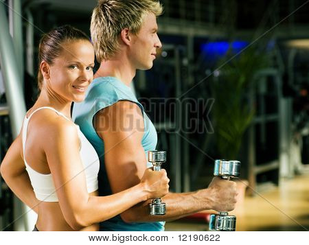 Fitness couple in the gym, rivaling each other, exercising with weights (focus on the face of the girl)