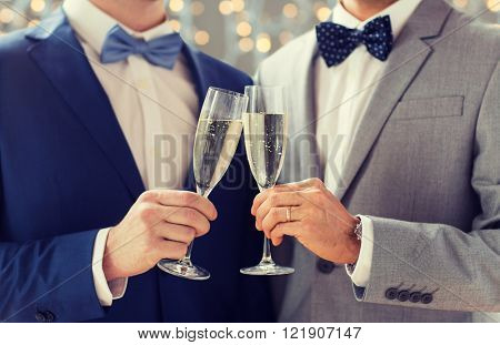 people, celebration, homosexuality, same-sex marriage and love concept - close up of happy married male gay couple drinking sparkling wine on wedding over holidays lights background