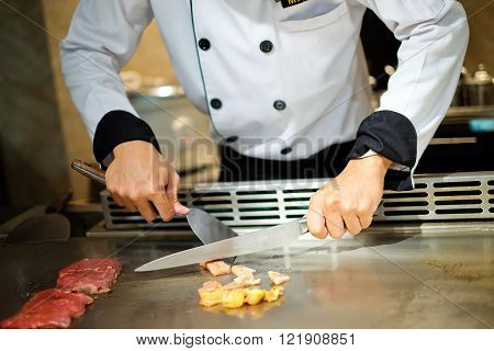 Japanese chef deliberately preparing and cooking traditional beef teppanyaki on a hot plate