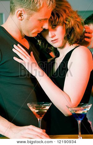 Couple flirting very obviously in a bar or at a club