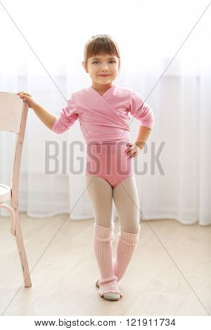 Little cute girl in pink leotard standing near chair at dance studio