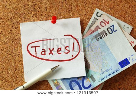 Taxes written and pinned to the board close up