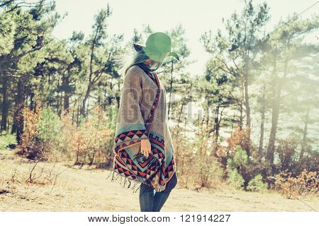 Fashionable girl in hat and poncho walking in forest among pine trees at sunny day