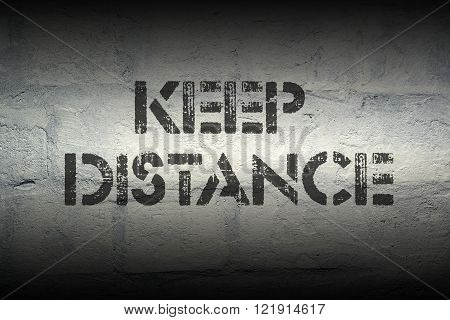 keep distance stencil print on the grunge white brick wall