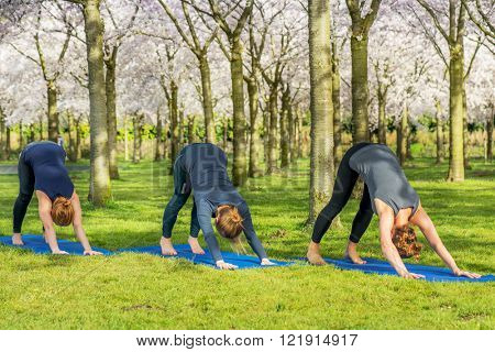Four young women practicing Lotus Pose for opening up the hips and creating flexibility in the ankles and knees