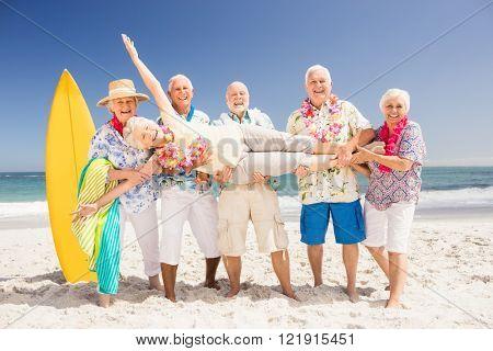 Senior friends holding senior woman on the beach