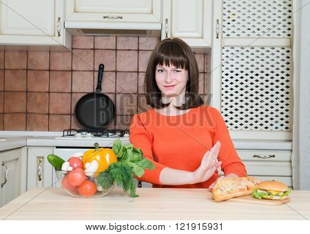Healthy and junk food concept - woman with vegetables rejecting hamburger and pizza. Diet. Weight loss.