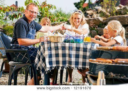 Familia tener una barbacoa en el jardín, comer