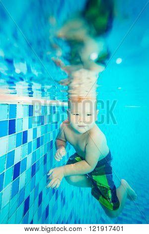 Cute caucasian boy enjoys of swimming underwater