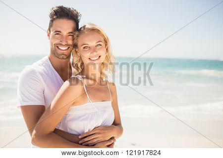 Smiling young couple hugging on the beach