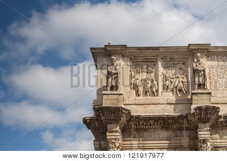 Details of the decorations of the Triumphal Arch beside Colosseum in Rome. Intense clouds on the blue sky.