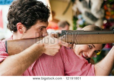 Couple in traditional German or Bavarian costume doing some target shooting at a gallery